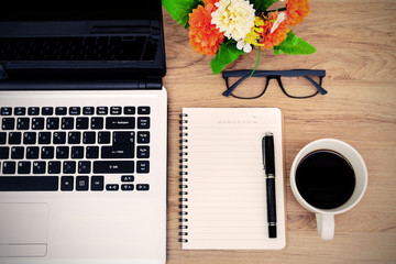 Laptop and cup of coffee with flower on desk