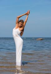 Young beautiful woman in white dress enjoyingsummer time