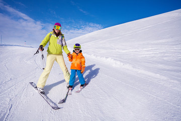 Mother and little boy learning to ski holding hand