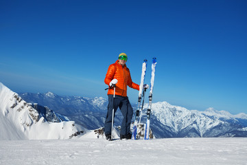 Man in ski mask stands and beautiful mountain view