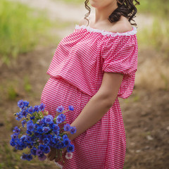 pregnant belly with a bouquet of cornflowers