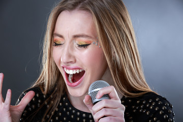 Portrait of a beautiful blonde young woman singing into micropho