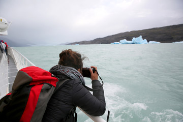 Tourist on boat taking picture of an Iceberg, Argentino Lake