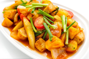 Fried vegetables with red sauce on white plate