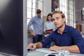 junger mann am arbeitsplatz schaut auf pc