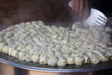 Cooking steamed traditional Nepalese momos in the street kitche