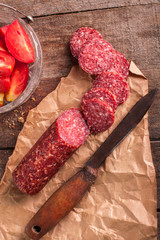 Salami on a paper with tomato
