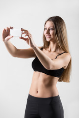 Smiling sporty girl taking selfie, self-portrait with smartphone
