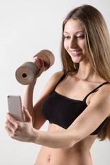 Smiling sporty girl holding dumbbell and taking selfie with smar
