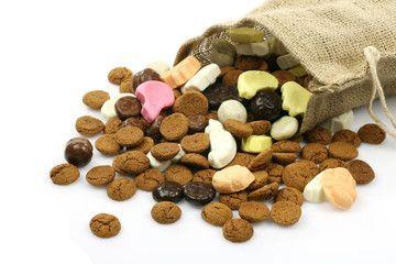 burlap sack with assorted colorful sweets on a white background
