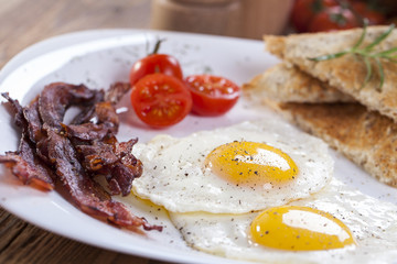 Fried egg and bacon on a plate with spices and vegetables