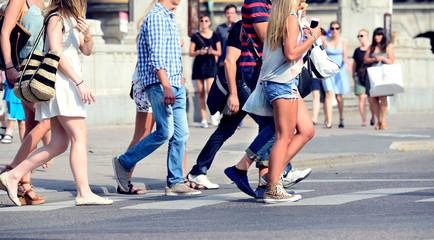 Sunlit summer pedestrians on zebra crossing
