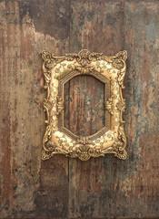 Baroque golden frame on wooden background. Grunge texture