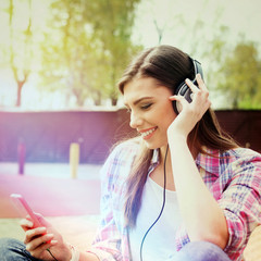 Teenage girl with headphones and smartphone in park in spring