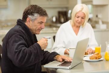 Mature couple having breakfast together man using laptop