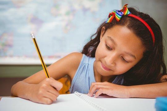 Little girl writing book in classroom