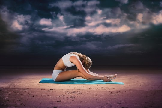 Gorgeous fit blonde in seated forward bend pose