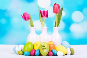 bunte ostereier mit tulpen in der vase