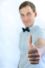 Smiling young man with thumb up in studio