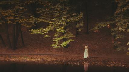 Beautiful woman in fairy forest near a stream