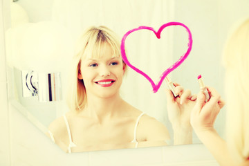 Woman drawing heart on a mirror.