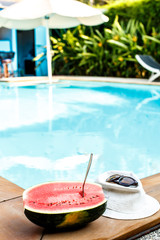 Watermelon and glasses near the pool