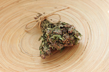 Bundle of dried thyme herb for tea on wooden plate