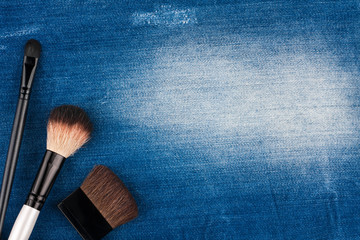 Three brushes for makeup lying on blue jeans