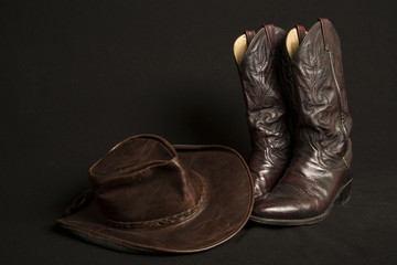 Cowboy boots and cowboy hat on black background