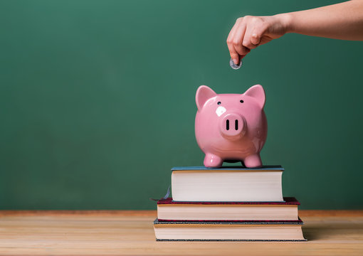 Depositing money in a piggy bank on top of books