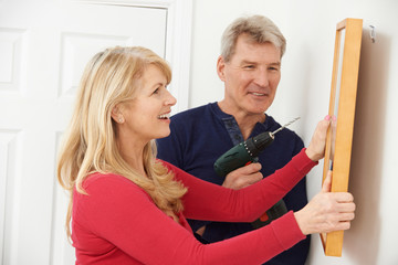 Mature Couple Drilling Wall To Hang Picture Frame