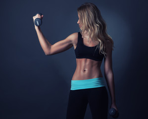 Woman with sport body in activewear doing exercise with dumbbell
