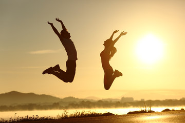 Fitness couple jumping happy at sunset