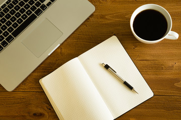 Laptop, notepad and coffee cup on wood table
