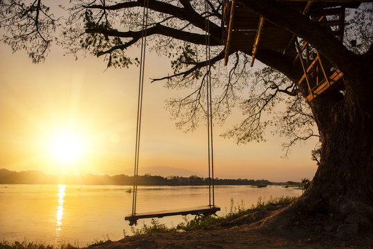 lone swing at river side and sunset ,Thailand