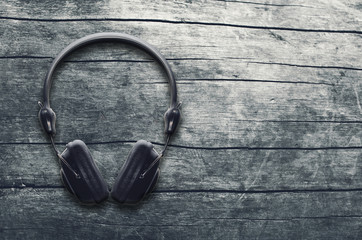 Music grunge background, black headphones on a wooden table