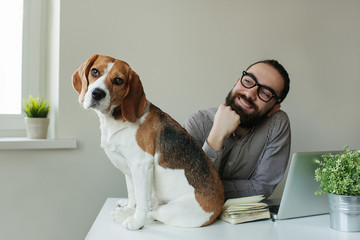 Smilling man in glasses with beagle on table