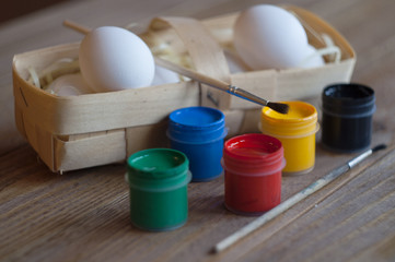 Eggs in the basket. Paints and brushes. Happy Easter.