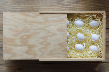 White eggs in a wooden box. Safe packing.