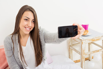 Happy young woman taking a selfie at home