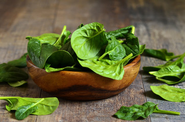 Spinach leaves in a wooden bowl.