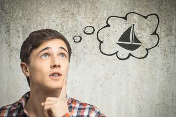 Junger Mann denkt an Segelboot