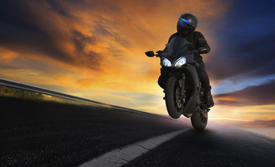 young man riding motorcycle on asphalt highways road with profes