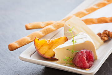 Slice camembert cheese with grilled peach, fresh raspberries and