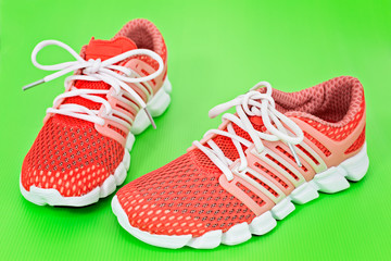 New orange and white running shoes, sneakers or trainers on gree