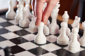 Hand with white pawn on chessboard