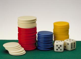 Fichas de poker y dados sobre un fieltro verde.