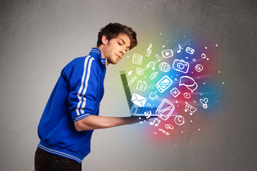 Casual man holding laptop with colorful hand drawn multimedia sy