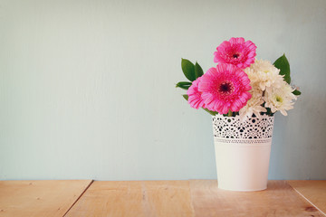 summer bouquet of flowers on the wooden table with mint backgrou