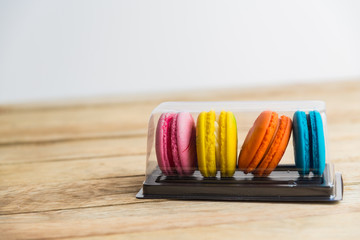 Colorful macaron in plastic box on wooden floor